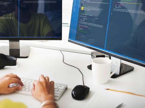 Web developer coding on dual screen rig